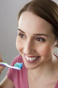 woman brushing teeth avoiding dental implant treatment